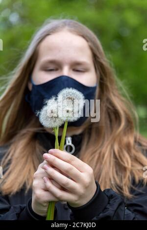Schoolgirl with a mask holding several dandelions - Stock Photo