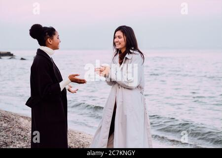Two beautiful girls in trench coats happily talking walking together on sunset beach
