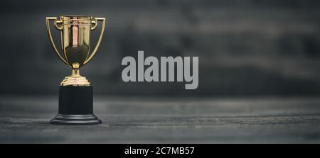 Champion golden trophy on black wooden background , Winning Cup concept.