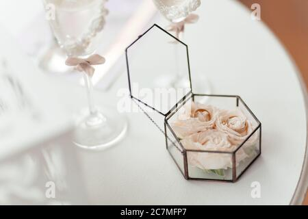 Wedding rings in the glass box filled with roses standing on the white table. Wedding accessories - Stock Photo