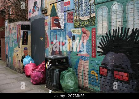 Rubbish and an interestingly-graffitied wall, Tib Street, corner of Foundry Lane, Northern Quarter, Manchester, England, UK - Stock Photo