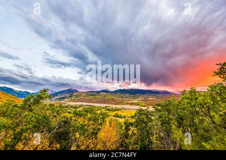 Aspen, Colorado rocky mountains colorful sunset orange red light in sky clouds wide angle high angle aerial view with storm clouds and foreground of p