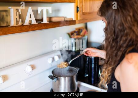 Young woman cooking pasta on rustic vintage stove top with stainless steel pot and steam in retro kitchen with eat sign decoration in farm house cotta