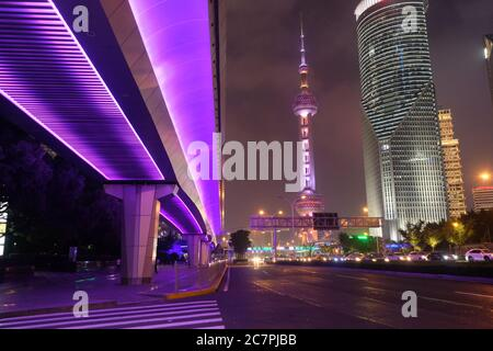 night scene of modern Shanghai Pudong. Highway under shining purple overpass. Famous Oriental Pearl TV Tower and buildings