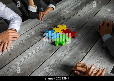 Business people team sitting around meeting table finishing assembling color jigsaw puzzle pieces unity cooperation ideas concept - Stock Photo