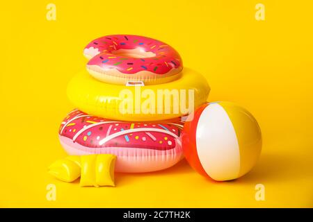 Inflatable rings, ball and arm floats on color background - Stock Photo