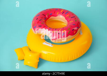 Inflatable rings and arm floats on color background - Stock Photo
