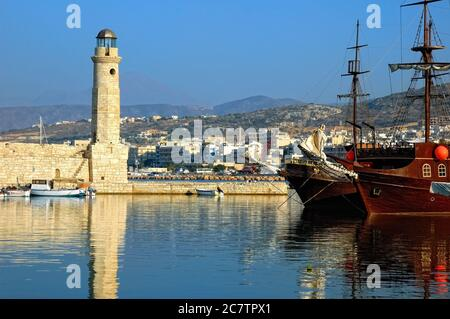 A view on the harbor at Rethymnon on the Greek isle of Crete. Historical marina old fortress wall with ancient lighthouse and replica of old ships at - Stock Photo