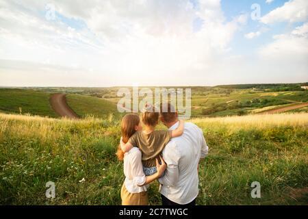 Happy family enjoying landscape outdoors in the field
