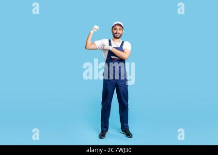 Full length happy expert handyman in blue overalls, cap and protective gloves pointing biceps, demonstrating strength. Profession of service industry, - Stock Photo