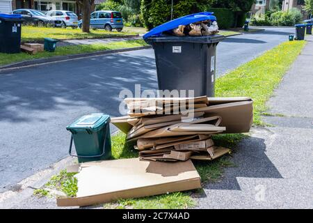 Roadside recycling wheelie bins and overflowing cardboard packaging awaiting refuse collection in a suburban street in Woking, Surrey, SE England - Stock Photo