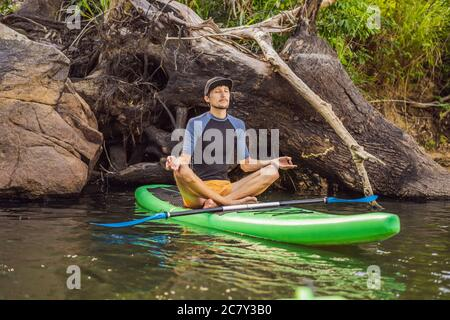 man practicing yoga on a SUP board during sunrise on a large river. Stand up paddle boarding - awesome active recreation in nature - Stock Photo