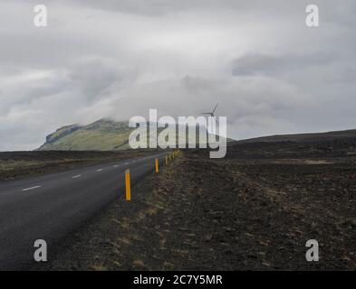 Asphalt road through empty northern volcanic landscape in iceland with Wind turbine and green hills covered by clouds, moody sky background, copy