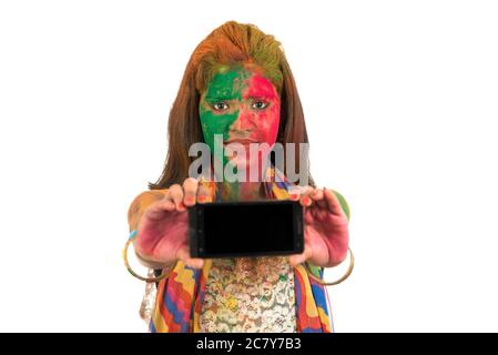 Young girl with colorful face showing smart phone screen on Holi festival. Festival and technology concept on white background. - Stock Photo