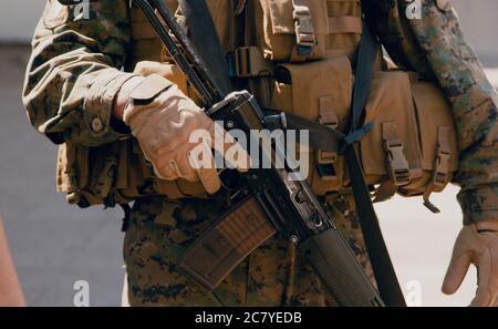 A soldier holding a gun near his waist - Stock Photo