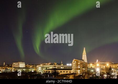 Green Northern Lights (Aurora Borealis) over the night skyline of Reykjavík with Hallgrímskirkja - Stock Photo