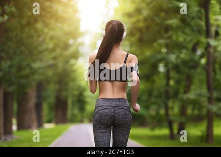 Back View Of Sporty Fit Young Woman Jogging In Green City Park