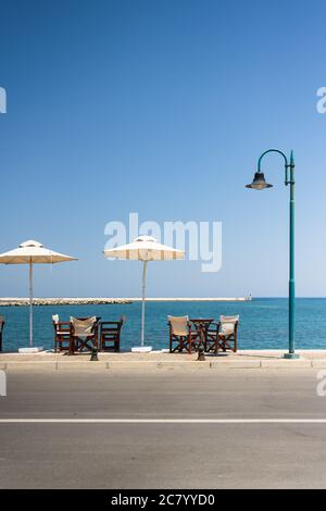 Tables, chairs and parasol of a restaurant in Skopelos with sunny holiday atmosphere with turquoise clear sea and blue sky. - Stock Photo