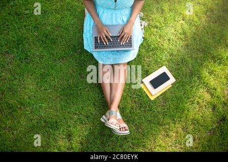 Unrecognizable black woman sitting on grass with laptop computer, working or studying online. Top view