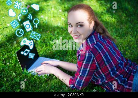 happy teenage girl lying on grass in park and using laptop with different applications - Stock Photo