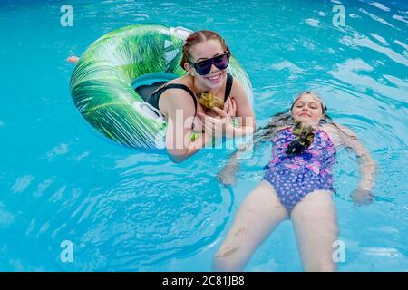 Girls in backyard above ground swimming pool with duckling - Stock Photo