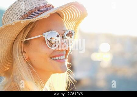 A blonde girl smiling with hat on - Beach and sunlight reflected in sunglasses - Beautiful young women in holidays - Portrait photo - Stock Photo