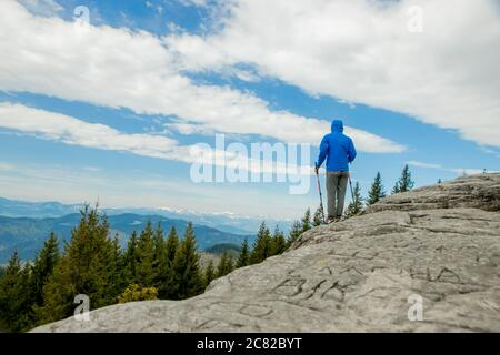 Young, carefree boy climbing up solid huge rocks, using poles to make it easy to reach the top, enjoying the view of natural wonders on the way - Stock Photo