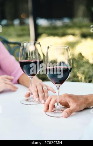 Close up photo of couple with glasses of red wine on date in restaurant outdoor - Stock Photo