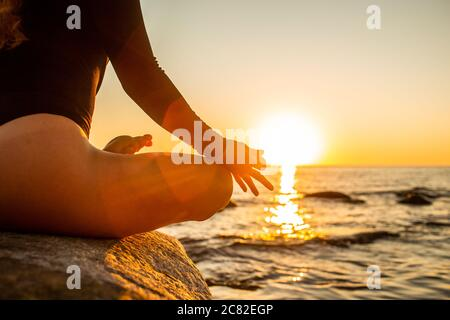 Hand of a woman meditating in a yoga lotus pose on the beach at sunset. Girl sitting on a warm rock