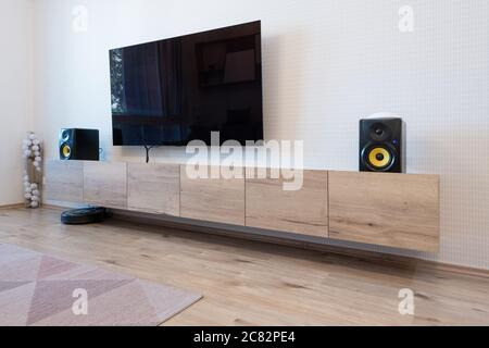 Cabinet and TV with speakers in living room of modern apartment