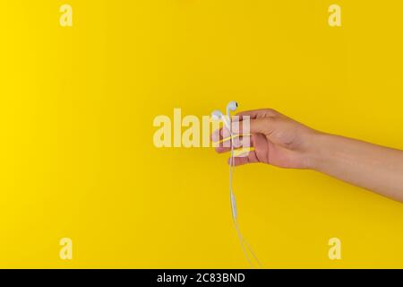 a person's hand holding portable wired earphones or headphones isolated against the colorful background, minimalism style, listen to the music - Stock Photo