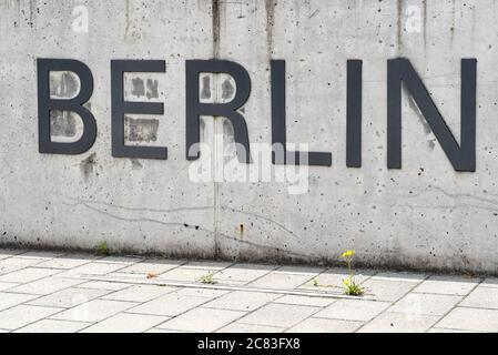 Berlin, Germany. 03rd July, 2020. The word 'Berlin' is attached to a concrete wall in front of a university building of Freie Universität in Dahlem. In front of it, a yellow flower grows from the pavement. It is part of the lettering 'Freie Universität Berlin'. Credit: Jens Kalaene/dpa-Zentralbild/ZB/dpa/Alamy Live News Stock Photo