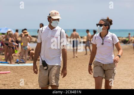 Torrenostra, Castellon, Spain - July 16, 2020: Beach assistants and attendants, work on the beach informing to help beachgoers to prevent coronavirus. - Stock Photo