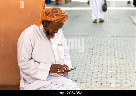 Mutrah, Oman - February 10, 2020: Omani adult man in traditional clothing with mobile in the street in Mutrah, Sultanate of Oman, Middle East