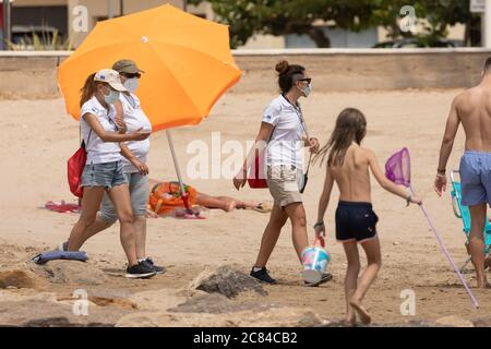 Torrenostra, Castellon, Spain - July 16, 2020: Beach assistants and attendants, work on the beach informing to help beachgoers to prevent the spread o - Stock Photo