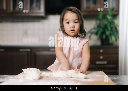 Pretty beautiful little girl is kneading dough on wooden chopping board - Stock Photo