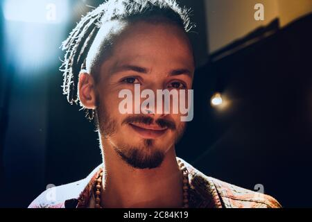 Close-up portrait of a young stylish man with dreadlocks