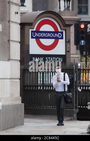 London, UK, 21 July 2020: A man in a face mask rubs hand sanitiser onto his hands as he exits the Underground at Bank station.  Despite Prime Minister Boris Johnson urging people to return to work, the City of London is almost deserted. Anna Watson/Alamy Live News - Stock Photo