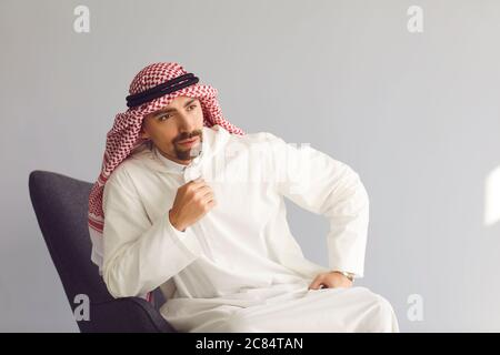 Pensive arab businessman sitting in a chair thinks looks up on a gray background. Portrait of an attractive arab man. - Stock Photo