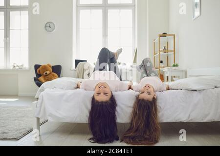 Cheerful mother and daughter with beautiful hair lying heads down on bed at home. Parent and kid having fun in bedroom - Stock Photo