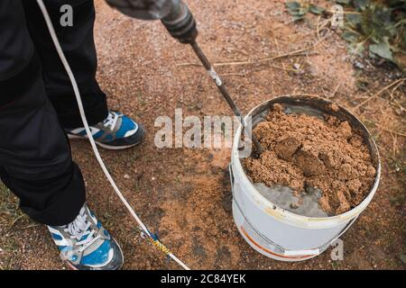 Preparation of cement glue mortar in a bucket of cement and sand using a mixer nozzle on a drill - the work of a professional bricklayer - Stock Photo