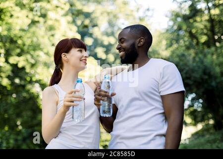 Happy cheerful multiethnic athletic couple, Caucasian woman and African man, with water bottles, communicating looking each other, after jogging or