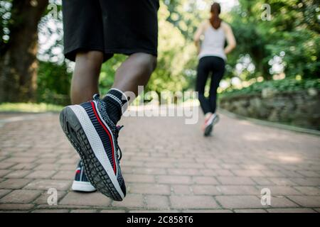 Close up back view photo of legs of African man in sport sneakers jogging in the city park on a sunny summer day, together with his female Caucasian