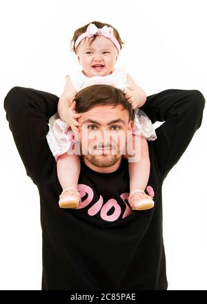 Vertical lifestyle portrait of a young dad with his baby daughter on his shoulders. - Stock Photo