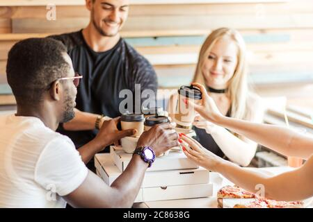 Group of young multiracial friends hanging out at a coffee shop. Young men and women meeting in a cafe having fun, eating pizza and drinking coffee