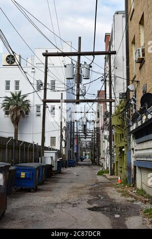 An urban alley way in Galveston, Texas.  The electric wires above disappear down the long side street which has dumpsters along on side and buildings.