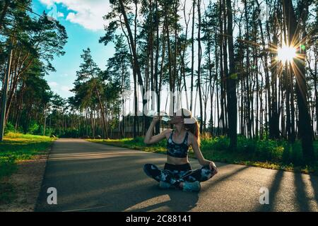 Young woman drinking water after jogging outdoors in forest. Healthy fitness girl sitting in lotus pose and drinking water