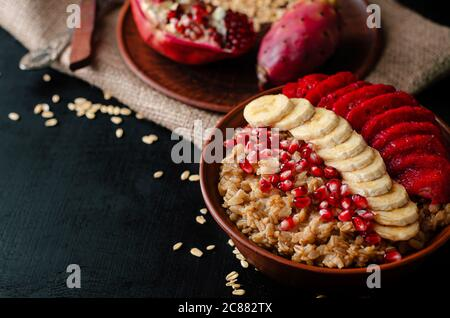 Healthy diet breakfast concept. Oat porridge with banana, pomegranate seeds and opuntia cactus fruit. - Stock Photo