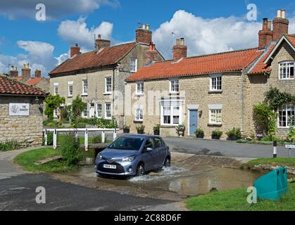 Toyota Yaris car crossing ford in the village of Hovingham, Ryedale, North Yorkshire, England UK - Stock Photo