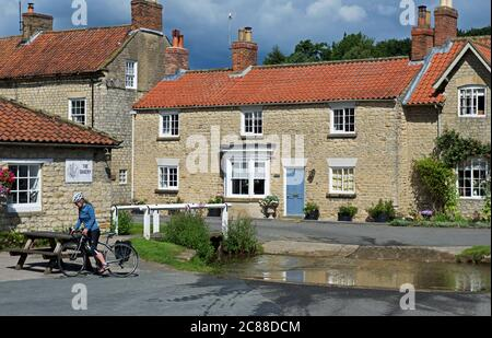 Young woman on bicycle in the village of Hovingham, Ryedale, North Yorkshire, England UK - Stock Photo